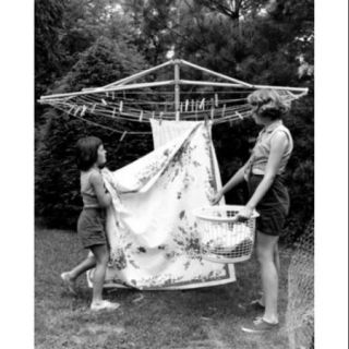 Mother and daughter hanging laundry in backyard Poster Print (18 x 24)